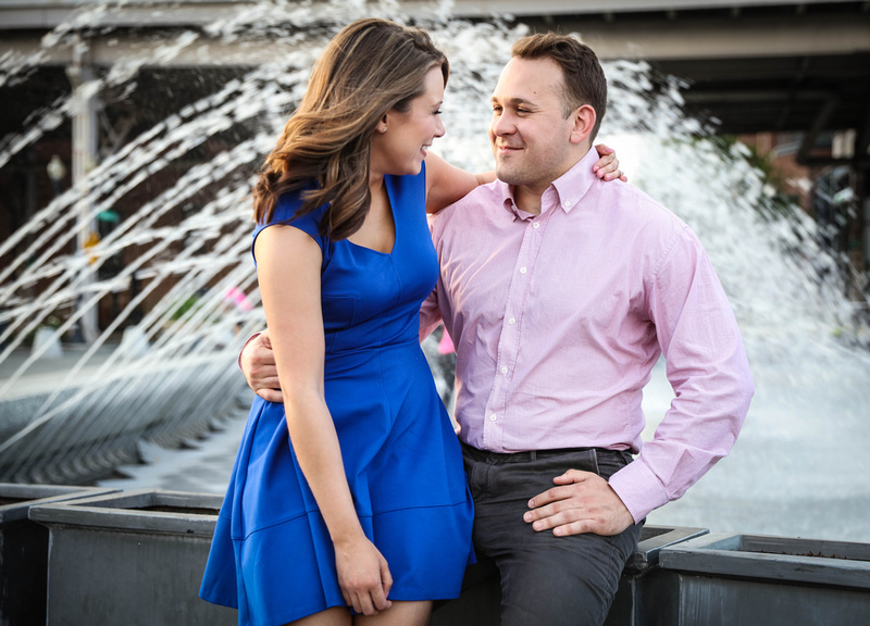 A young woman sits on her fiancé's lap and smiles, in front of a spraying fountain. engagement photography