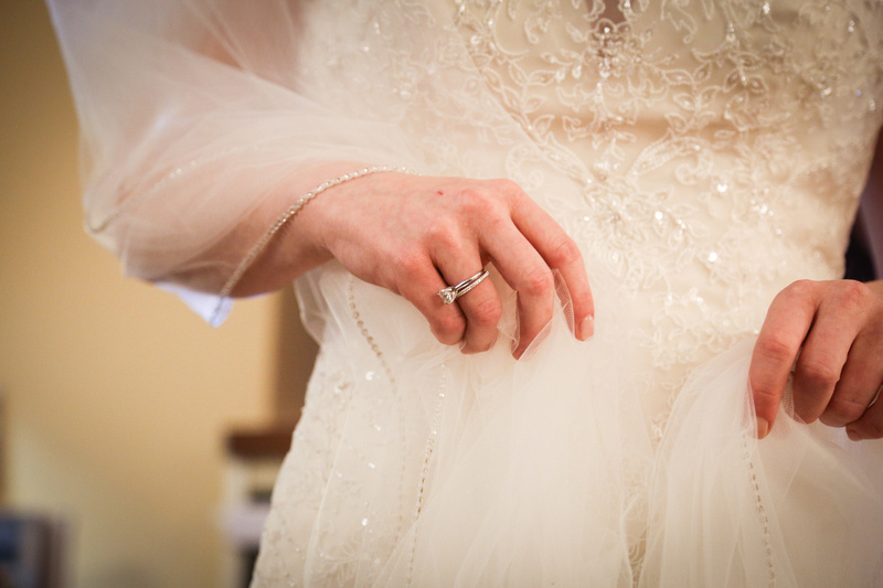 Wedding photography, a closeup of an engagement ring worn by a bride in a white gown with beaded embellishment.