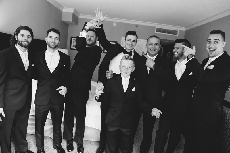 Wedding photography, 7 men and a young boy wearing black tuxedos are laughing.