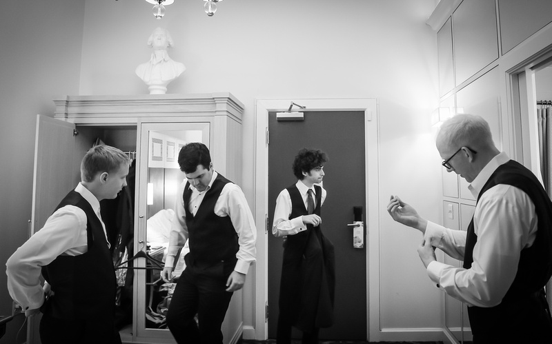 Wedding photography, a groom and his groomsmen put on their suits in a hotel room.