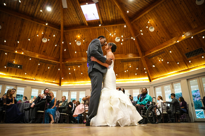 Wedding photography, the bride and groom embrace during their first dance under a wooden ceiling.