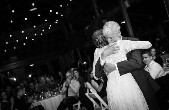 Wedding photography, a bride hugs her father sweetly.