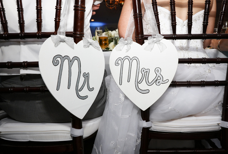 Wedding photography, two signs that say Mr. and Mrs. hang on the back of a bride and groom's chairs.