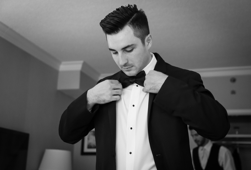Wedding photography, a dark haired man in a tuxedo straightens his jacket.