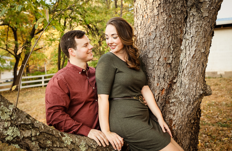 Engagement photography: a young woman in a green dress sits on a tree. Her fiancé smiles at her.