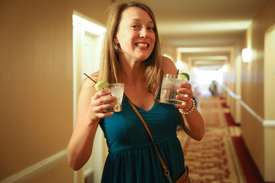 Wedding photography, a bridesmaid grins with two cocktails in her hands.
