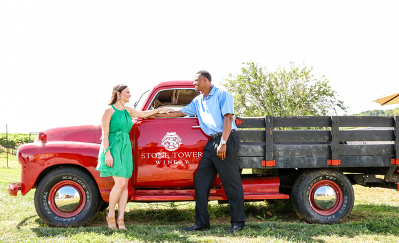 Engagement photography: a woman in a green dress and a man in a blue shirt stand beside a red farm truck.
