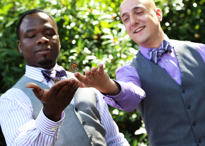 Two grooms form this beautiful inter-racial married couple. Both have their hands extended as a butterfly hovers just above.