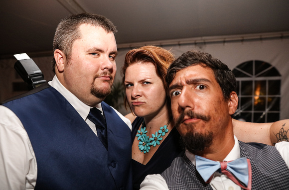 Wedding photography, a groom stands with his wedding photographers, making fierce faces.