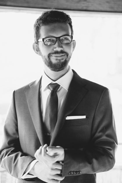 Wedding photography, a groom in glasses and a grey suit smiles.