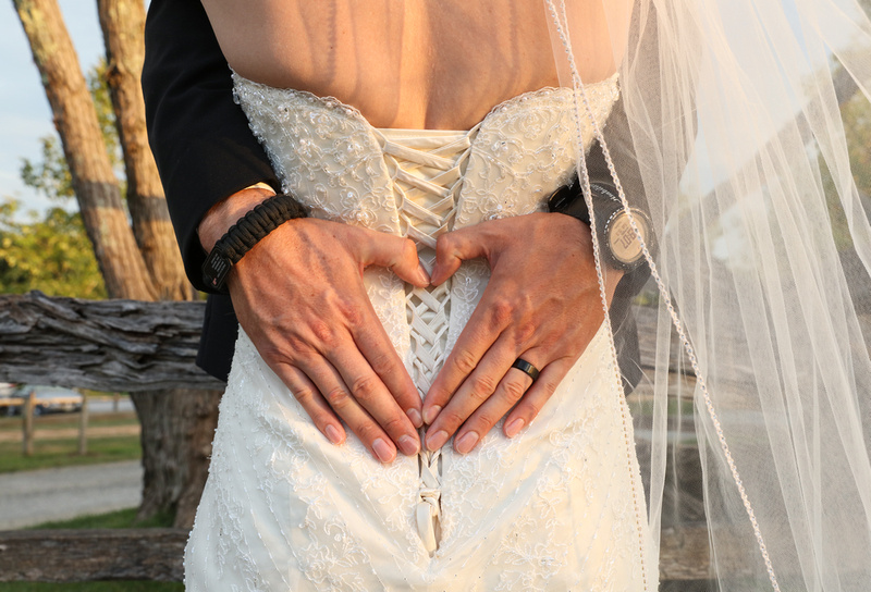 Wedding photography, a close-up shot of the groom's hands on the bride's back, in the shape of a heart.