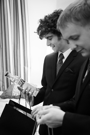 Wedding photography, groomsmen smile while holding their wedding gifts.