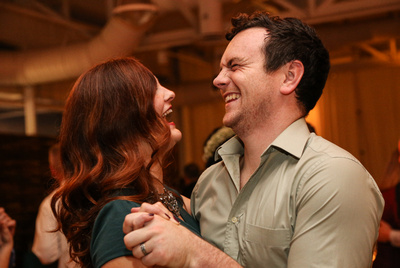 Wedding photography, a couple laughs out loud while dancing together. She has red hair.