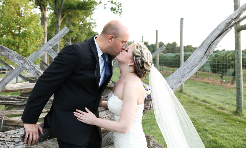 Wedding photography, a bride and groom kiss while leaning on a historic wooden fence.