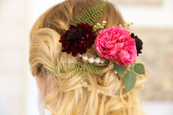 Bride wearing decorative, floral hair piece at the back of her head. Pink, marroon flowers, pearls and leaves. Designed by Flower Haus Guys
