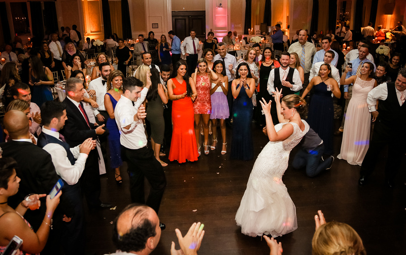 Wedding photography, the bride and groom dance with a big crowd surrounding them.
