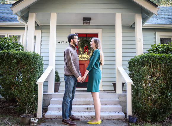Wedding photography, a couple holds hands in front of their home. She wears a green dress.