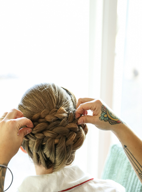 Wedding photography, a hairstylist with colorful tattoos fixes a bride's hair.