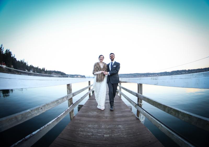 Wedding photography, a fisheye shot of a couple walking down a dock towards the camera.