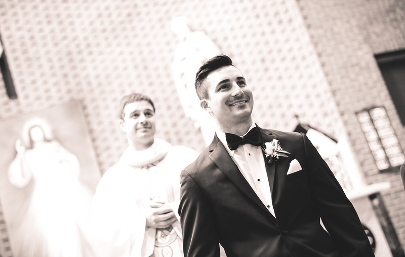 Wedding photography, a beaming groom awaits his bride. The priest stands behind him.